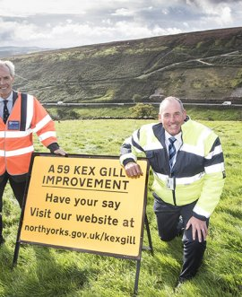County Councillors Don Mackenzie and Stanley Lumley with the A59 at Kex Gill in the background