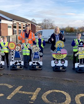 Children from Ainderby Steeple Primary School give the new signs the thumbs-up along with staff member Laura Hollinshead and Kevin Pratt, North Yorkshire County Council road safety officer