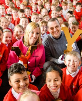 Teachers Mrs Fenby and Mr Appleby holding the Tour de Yorkshire men's and women's trophies, surrounded by children from Filey Junior School.