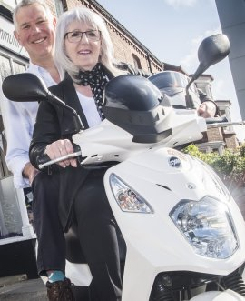 Councillor Caroline Dickinson and Andy Reddick with the new scooter.