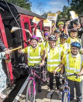 Pupils from St Joseph's School hand the baton to road safety champions Janet and David Warin at Pickering station.