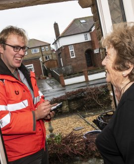 Postman Christian Elcoate checks in on Safe and Connected customer Brenda Simpson