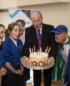 County Councillor Patrick Mulligan helped by school pupils to present Power Down Pete with his birthday cake
