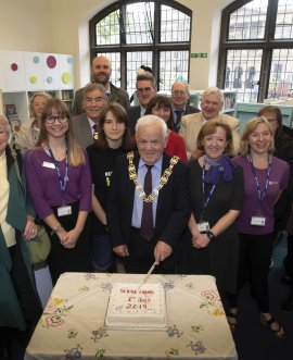 Cllr Jim Clark cuts the cake watched by staff and volunteers