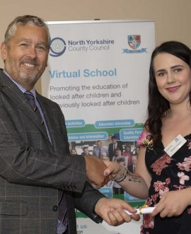Stuart Carlton presents a graduation certificate to Keeley Clayton