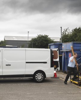man unloads material from white van at recycling centre