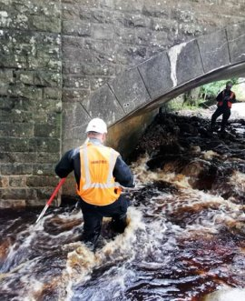 Divers inspect a bridge over Barney Beck that runs into the River Swale west of Reeth