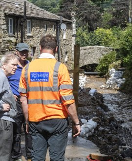 A County Council highways officer discusses deployment of sandbags with local residents