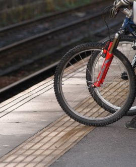 Cyclist waiting for train at platform edge