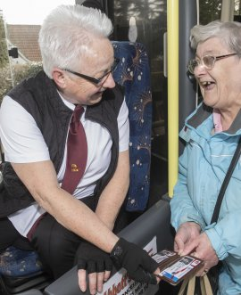 Elderly lady using bus pass on bus