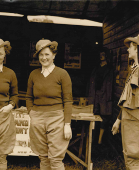 Winifred (left) and her sister Dorothy (centre) at a Women's Land Army recruitment stand.