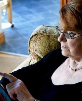 A lady in a care home using a tablet