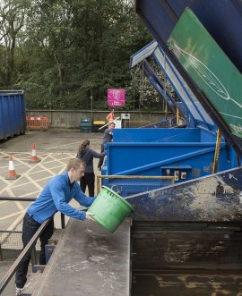 A man tips garden waste at a Household Waste Recycling Facility